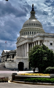 Photo of cloudy sky behind Senate side of Capitol complex with leafy tree in right foreground and American flag in distant left rearground.